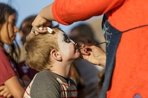 A child gets his face painted by a volunteer during the 4th Annual Earth Day Extravaganza aboard the Marine Corps Air Ground Combat Center, Twentynine Palms, Calif., April 13, 2018. The purpose of the extravaganza is to bring families together and educate them on how to be better stewards of the Earth's resources. (U.S. Marine Corps photo by Lance Cpl. Rachel K. Porter)
