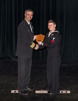 Capt. Howard Markle, Puget Sound Naval Shipyard & Intermediate Maintenance Facility commander, presents ND1 (DWS/EXW) Eric Lehman, a diver with PSNS & IMF Everett Detachment, with the PSNS & IMF Everett Detachment's Junior Sailor of the Year Award during the Employee of the Year Ceremony, March 29, 2018, at the Admiral Theatre in Bremerton, Washington. (U.S. Navy photo by Carie Hagins, PSNS & IMF photographer)