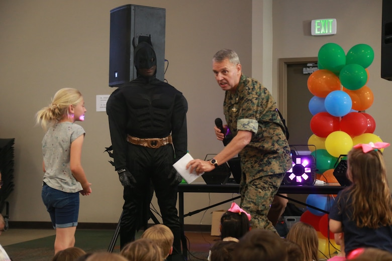 Lt. Cmdr. Greg Uvila, regimental chaplain, 7th Marine Regiment, and Batman welcome a child up to the stage at the Child Abuse Awareness and Military Child Appreciation Carnival aboard the Marine Corps Air Ground Combat Center, Twentynine Palms, Calif., April 12, 2018. The event was held to provide available resources to community members and hold a small fair for children. (U.S. Marine Corps photo by Lance Cpl. Preston L. Morris)