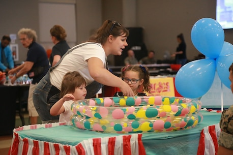 A mother helps her children play a carnival game at the Child Abuse Awareness and Military Child Appreciation Carnival aboard the Marine Corps Air Ground Combat Center, Twentynine Palms, Calif., April 12, 2018. The event was held to provide available resources to community members and hold a small fair for children. (U.S. Marine Corps photo by Lance Cpl. Preston L. Morris)