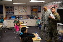 Air Force Maj. Courtland Pitt, left, a Chaplin with 110th Medical Group, introduces Marine Corps Cpl. Chandarong Ouk, right, an embarkation specialist with 4th Medical Battalion, 4th Marine Logistics Group, to a classroom of students during a career day at the Kotzebue Elementary School, Kotzebue, Alaska, April 19, 2018.