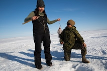 Marine Corps Sgt. Veronica J. Rios, right, an embarkation specialist with 4th Medical Battalion, 4th Marine Logistics Group, learns how to ice fish on the Kotzebue Sound from Puyuk Joule, a local member of the community during Innovative Readiness Training Arctic Care 2018, Kotzebue, Alaska, April 19, 2018.