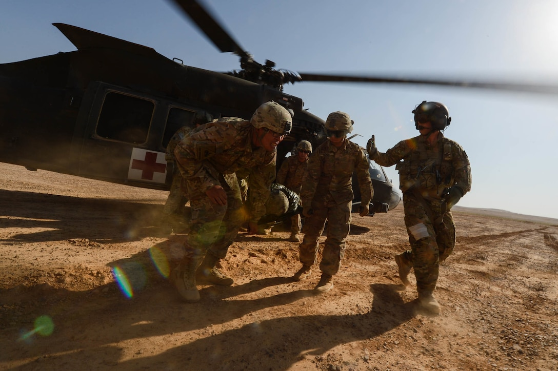 Soldiers run away from a helicopter carrying a stretcher on desert-type terrain.