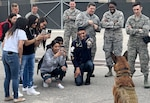 South San Antonio High School students take pictures of Balto, an 802nd Security Forces Squadron military working dog, during a Troops for Teens event at Joint Base San Antonio-Lackland March 9. Troops for Teens, a joint SSAHS and Air Forces Cyber volunteer program, links Airmen mentors with at-risk teens.
