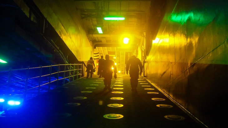 Two Marines walk up a ramp on a ship, with blue, yellow and green lights illuminating the path.