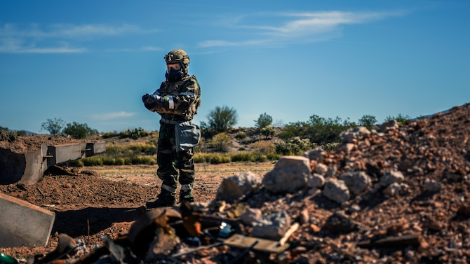 A explosive ordnance disposal technician from the 355th Civil Engineer Squadron assesses the fallout of a disarmed improvised unexploded ordnance during a training exercise at Davis-Monthan Air Force Base, Ariz., March 28, 2018. The exercise involved the discovery, assessment and disposal of unexploded ordnance on a mock runway. (U.S. Air Force photo by Airman 1st Class Michael X. Beyer)