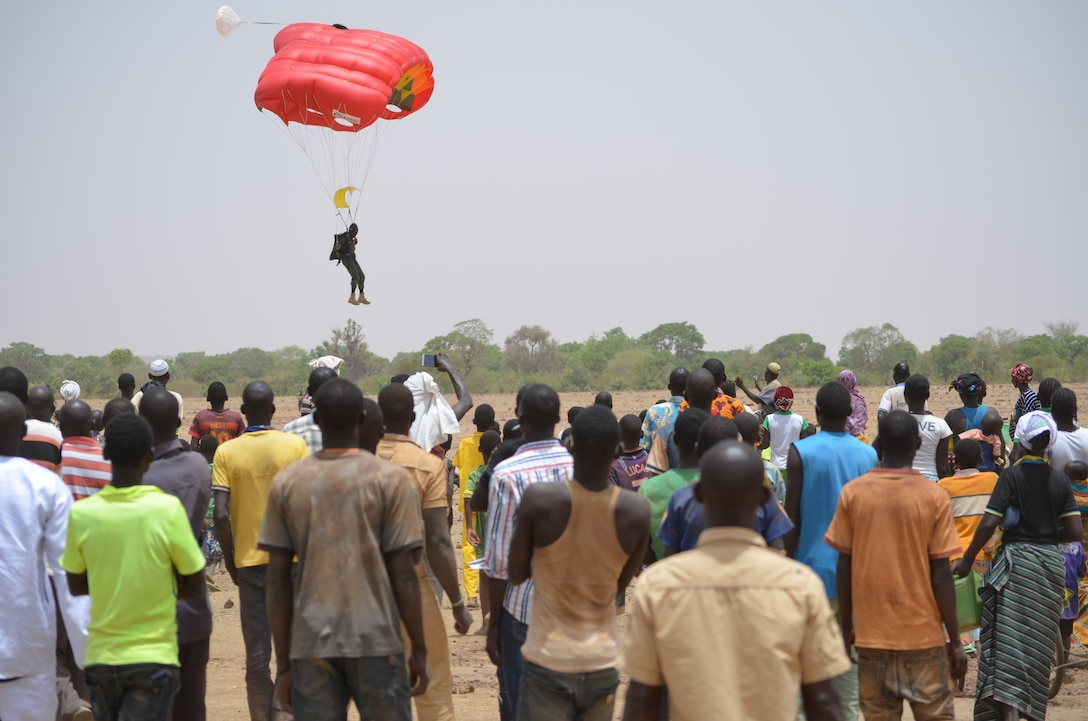 A member of the Burkinabe free fall team lands in front of local villagers.