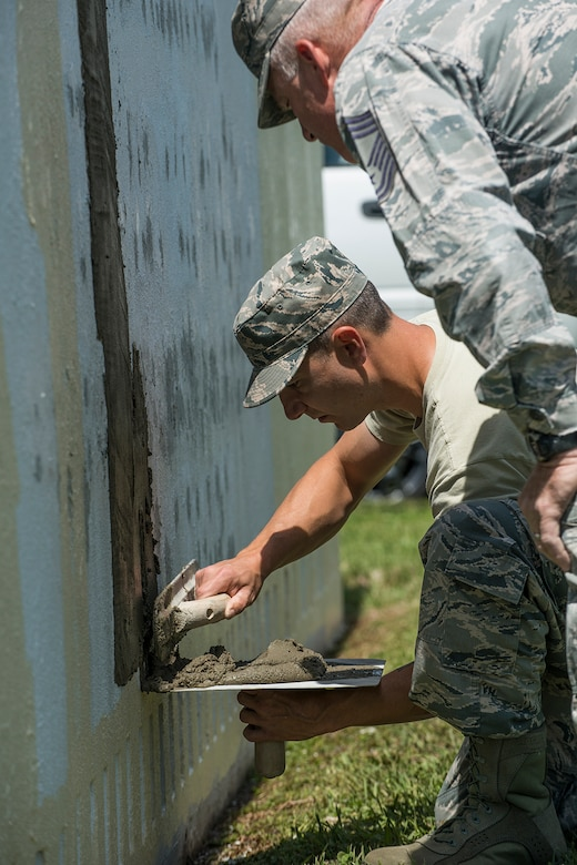 An Airmen assigned to the 307th Civil Engineer Squadron is learning how to evenly and smoothly spread concrete to fill holes in the 307th Bomb Wing headquarters sign on April 11, 2018, Barksdale Air Force Base, La.
