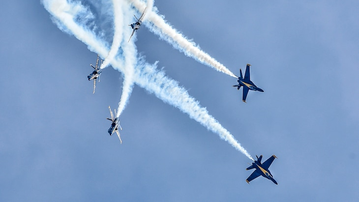 Five jets fly in different directions while perform a stunt.