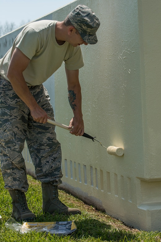 An Airman assigned to the 307th Civil Engineer Squadron applies a fresh coat of paint to the 307th Bomb Wing headquarters sign on April 11, 2018, Barksdale AFB, La.