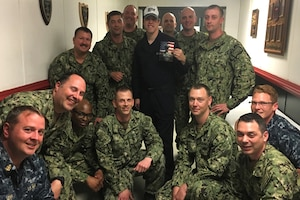 Sailors pose for a photo with a NASCAR driver.