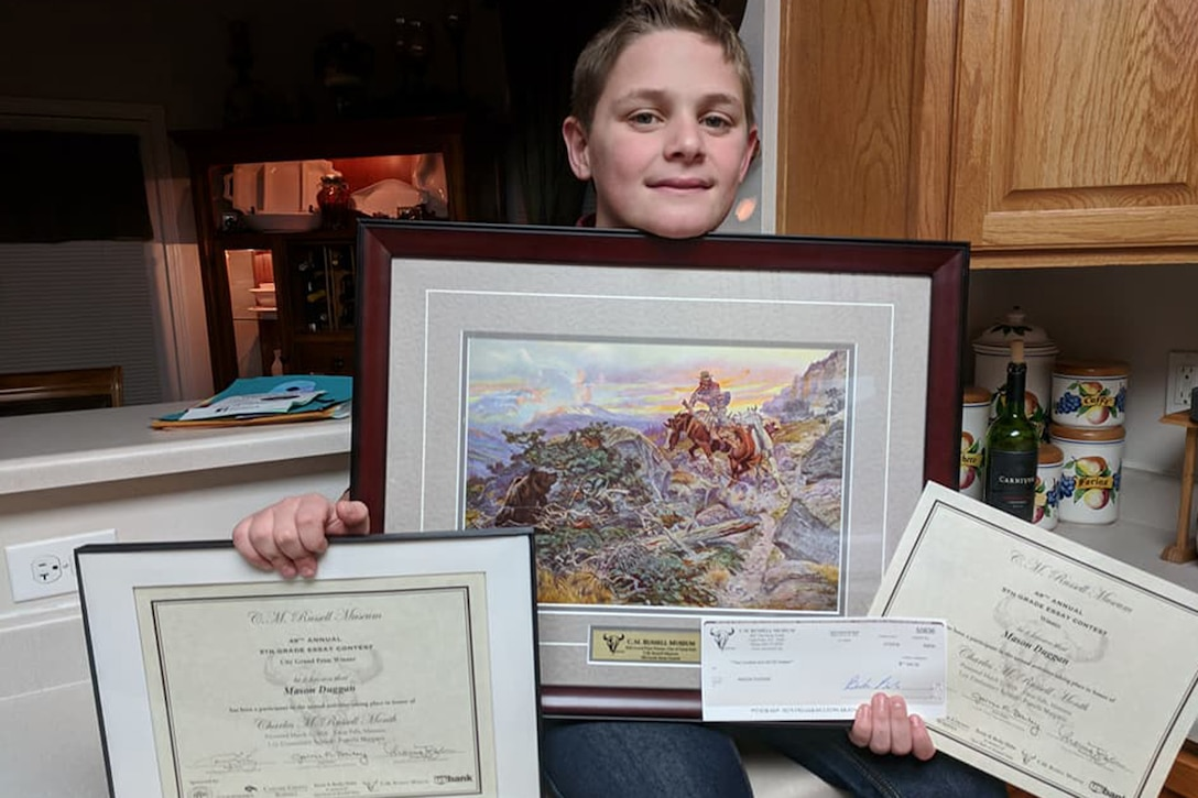 Mason Duggan, son of Lt. Col. Jerrod Duggan, 341st Maintenance Group deputy commander, poses with award certificates March 2, 2018, in Great Falls, Mont.