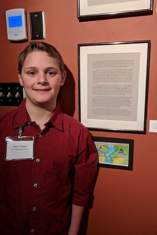 Mason Duggan, son of Lt. Col. Jerrod Duggan, 341st Maintenance Group deputy commander, poses next to his essay displayed at a museum March 2, 2018, in Great Falls, Mont.
