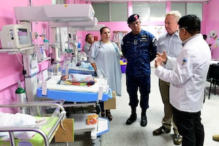 Military officials tour a clinic.