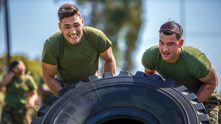 Two Marines push a tire in an effort to flip it.