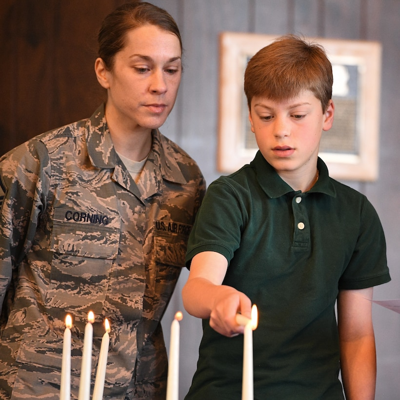 Evan Corning lights candles alongside his mother, Master Sgt. Michele Corning, during the Holocaust Days of Remembrance Service April 18, 2018, at Hill Air Force Base, Utah. The event's guest speaker was Diane Warsoff, a resident of Utah and second-generation Holocaust survivor. (U.S. Air Force photo by R. Nial Bradshaw)