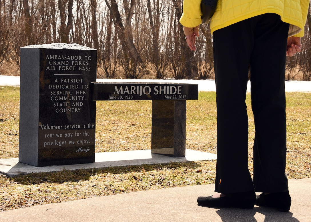 """A friend of the late Marijo Shide, Grand Forks Air Force Base Ambassador, admires the new dedicated bench on behalf of Shide, April 20, 2018, on Grand Forks AFB, N.D. More than 50 Airmen, ambassadors, friends and family members gathered in honor of Shide, who lived as an example of her motto, """"Volunteer service is the rent we pay for the privileges we enjoy."""" (Air Force photo by Airman 1st Class Elora J. Martinez)"""