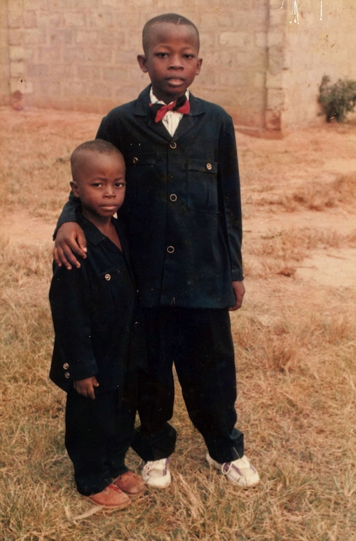 "Airman 1st Class Kofi Combey Douhadji, 92nd Logistics Readiness Squadron vehicle operator, poses for a photo with his younger brother in Togo, where he lived until his family was selected by the online Diversity Visa Program to immigrate the U.S. The program provides a limited number of visas each fiscal year to a class of immigrants known as ""diversity immigrants"" from countries with historically low rates of immigration to the U.S. (Courtesy Photo)"