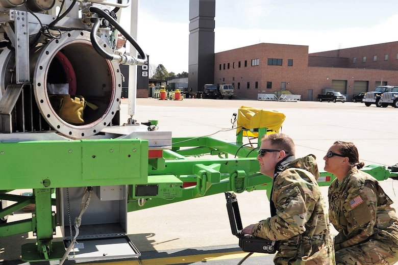 Staff Sgt. Michael Allen, a 731st Airlift Squadron C-130 Hercules aircraft loadmaster, makes adjustments to a USDA Forest Service Modular Airborne Fire Fighting System aircraft loading trailer while Senior Master Sgt. Nattessa Gilbert, a 731st AS loadmaster and MAFFS trainer, offers instruction at Peterson Air Force Base, Colorado, April 19, 2018.