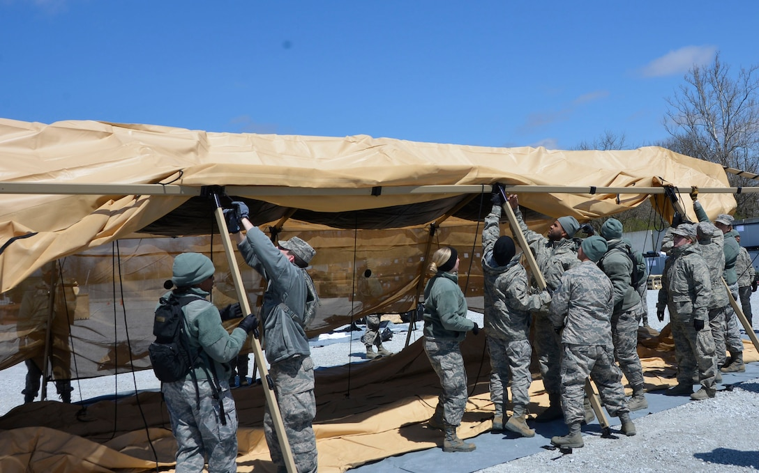 Members of the 81st Medical Group put up a tent side during the Expeditionary Medical Support field confirmation exercise at Camp Atterbury, Indiana, April 17, 2018. The confirmation exercise evaluated the tactics, techniques and procedures of EMEDS operations during a domestic U.S. contingency such as a natural disaster. (U.S. Air Force photo by Mary McHale)