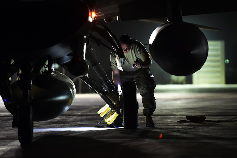 an airman places a yellow tire chalk behind the back wheel of an f-16 fighting falcon at night