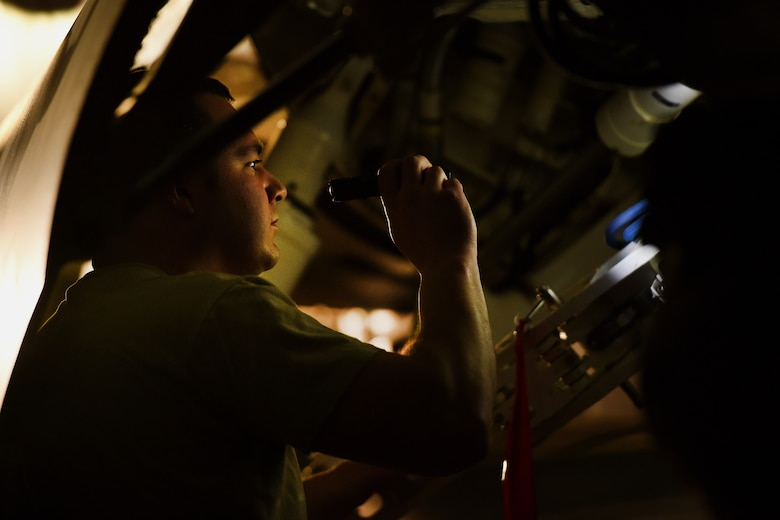 an airman holds a flash to inspect and f-16 fighting falcon