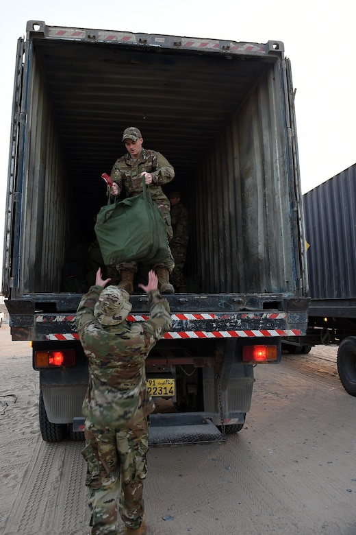 An airman inside a large truck hands a green mobility bag to another airman on the ground