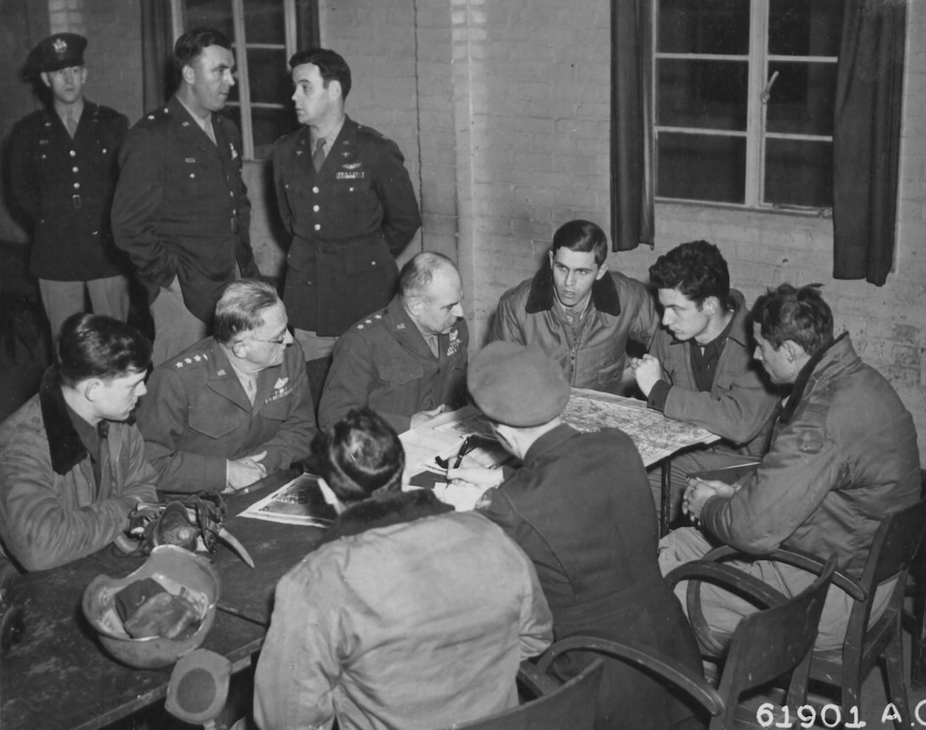 Gen Spaatz (2nd from left) and Lt Gen Doolittle (3rd from left) discuss results of a bombing attack with Eighth Air Force Airmen who just returned from the mission (note armored helmet and oxygen mask on the table).