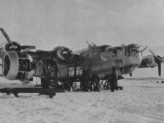 Ground crew changing an engine on a B-24 in the snow at an Eighth Air Force base in England.  Most maintenance was done outdoors regardless of the season or weather.