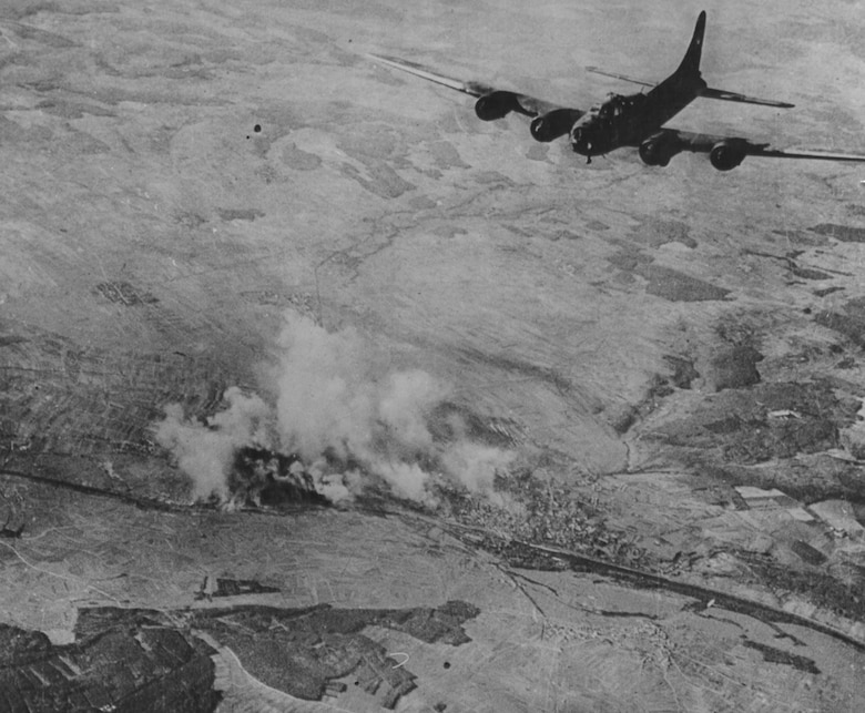 Schweinfurt in flames while a B-17 heads for home Black Thursday after bombing.