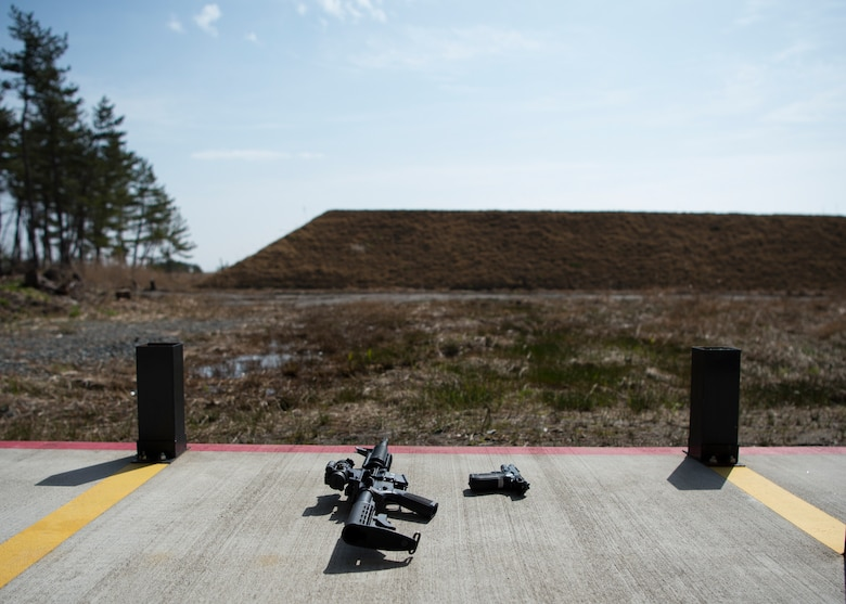 An M4 carbine and an M9 pistol sit on the ground of the new 35th Security Forces Squadron Combat Arms Training and Maintenance outdoor firing range at Draughon Range adjacent Misawa City, Japan, April 18, 2018. Conceptualized nearly three years ago, the outdoor range provides CATM six times more space to qualify Airmen on a variety of weapons. The current indoor range can qualify seven Airmen at one time, where the outdoor range serves 40. (U.S. Air Force photo by Staff Sgt. Deana Heitzman)