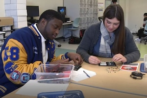 Two students sit at a table and work on a project.