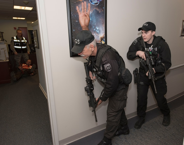 Ralph Marschhausen and Matthew Nolan, Security guards with the 23rd Space Operations Squadron, prepare to clear the 23rd SOPS command section office in Building 100 at New Boston Air Force Station, New Hampshire, April 10, 2018. Marschhausen and Nolan swiftly responded to the active shooter threat exercise scenario, conducted by the 50th Space Wing Inspector General's office during their inspection visit to the wing's geographically separated unit.