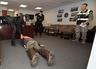 Ralph Marschhausen and Matthew Nolan, Security guards with the 23rd Space Operations Squadron, secure the simulated active shooter, in the 23rd SOPS command section office in Building 100 at New Boston Air Force Station, New Hampshire, April 10, 2018. The 50th Space Wing Inspector General's office conducted a short sprint active shooter exercise during their inspection visit to test the readiness of the wing's geographically separated unit.