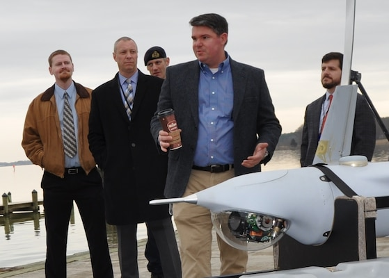 IMAGE: DAHLGREN, Va. (March 28, 2018) - Navy scientist Dr. Chris Weiland briefs visitors on the coordinated use of unmanned aerial vehicles for intelligence and targeting at a demonstration of the Surface and Expeditionary Warfare Mission Module that will be integrated in the developmental Common Unmanned Surface Vehicle (CUSV). The mission module comprises engagement system technology developed by Naval Surface Warfare Center Dahlgren Division coupled with a Battle Management System that controls munitions such as the Longbow Hellfire Missile. The event comes on the heels of a cooperative research and development agreement that NSWCDD signed with Textron Systems who makes the CUSV. The agreement covers the integration of missile, designator, and remote weapon station payloads to the CUSV with its 3,500-pound payload capacity on the deck and a payload bay measuring 20.5 x 6.5 feet.  (