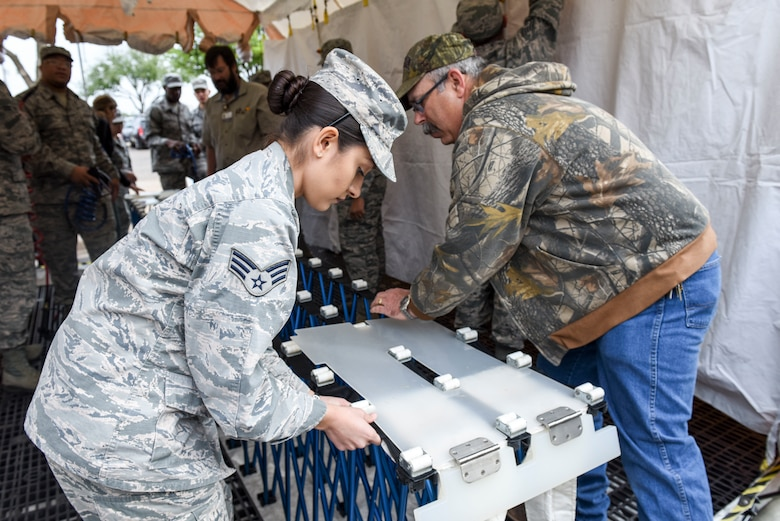 U.S. Air Force Senior Airman Anallely Mendoza Cuevos, 17th Medical Group lab technician, works with San Angelo Community Medical Center nurse, Todd Castlebury, to assemble the patient litter conveyor at the San Angelo Community Medical Center, San Angelo, Texas, April 19, 2018. The patient litter conveyor allows individuals who cannot walk to be transported through the decontamination tent using this conveyor in the event of an emergency.  (U.S. Air Force photo by Aryn Lockhart/Released)