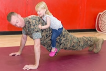 Captain Kendall Ignatz decides that normal push-ups are not enough and allows his daughter to sit on his back to create more resistance during the Big Marine Little Marine High Intensity Tactical Training (HITT), held in the Semper Fit gym, aboard Marine Corps Logistics Base Barstow, Calif., April 18.