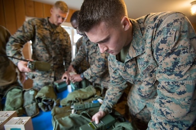 Lance Cpl. Wyatt Dillon, a radio operator with 4th Air Naval Gunfire Liaison Company, Force Headquarters Group, tests a radio as part of a gear accountability check, in Durness, Scotland, April 22, 2018.