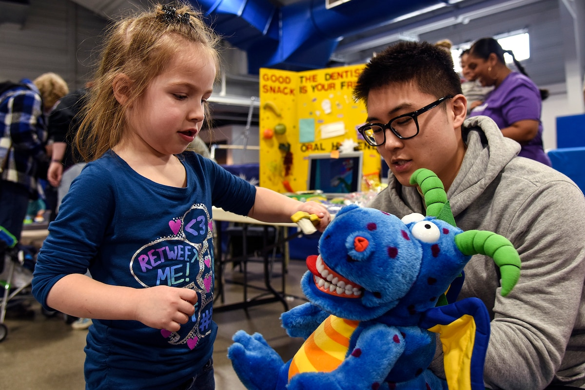 A girl brushes a blue dragon stuffed animal's teeth as an airman observes.