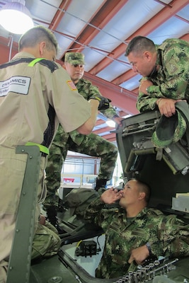 U.S. Army Sgt. Diego Franco translates from English to Spanish for Judson Hockman of General Dynamics Land Systems on M1135 Stryker maintenance during a State Partnership Program subject matter expert exchange April 18, 2018. Five soldiers from the Colombian army spent a week with Soldiers from the South Carolina Army National Guard during the exchange on maintenance best practices.