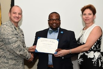 Dr. Norris Williams, Sumter School District leadership and school excellence assistant superintendent, center, receives a certificate of appreciation from Col. John Bosone, 20th Fighter Wing vice commander, left, and Jane Allen, 20th Mission Support Group installation support deputy director, during an annual volunteer recognition ceremony at Shaw Air Force Base, S.C., April 19, 2018.