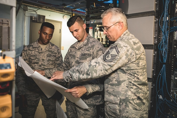 U.S. Air Force Senior Master Sgt. Mark Buchanan, right, superintendent, Staff Sgt. Charles Chalk, center, cable and antenna technician, and Staff Sgt. Wilson Gardner, airfield systems technician, from the 202d Engineering Installation Squadron (EIS), Georgia Air National Guard (ANG), review technical drawings at Muñiz ANG Base in San Juan, Puerto Rico, April 19, 2018. The 202d EIS deployed to the Puerto Rico Air National Guard's 156th Airlift Wing as part of the Hurricane Irma and Maria recovery efforts to spearhead a large-scale project relocating communications systems cabling and equipment to a new hardened facility.