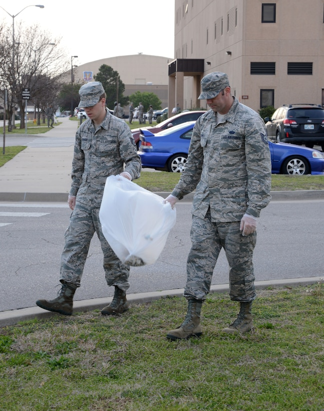 Staff Sgt. Nick Howard and Tech. Sgt. Travis Rowell, with the 552nd Air Control Network Squadron, teamed up to clean the grounds around the 552nd Air Control Wing during Tinker Pride Day Apr. 13, 2018.