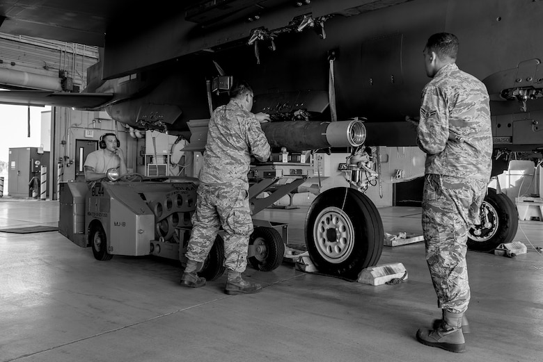 Airman 1st Class Kyle Shaw (left), Staff Sgt. Casey Chilcote, and Airman 1st Class Dylan Davis, 4th Aircraft Maintenance Squadron load crew members, load a training weapon onto an F-15E Strike Eagle, April 20, 2018, at Seymour Johnson Air Force Base, North Carolina.