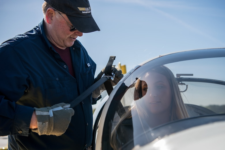 """William """"Boo-boo"""" Miller (left), Controller Appreciation coordinator, helps Senior Airman Payton Rossi, 4th Operations Support Squadron air traffic controller, into his RV9A aircraft, April 21, 2018, in Pikeville, North Carolina."""