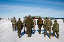 Distinguished visitors from Marine Forces Reserve and other service branches walk the snowy streets of Noatak, Alaska, as they visit the service members of Innovative Readiness Training Arctic Care 2018, Noatak, April 21, 2018.