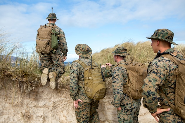 Lance Cpl. Wyatt Dillon (left), radio operator with 4th Air Naval Gunfire Liaison Company, Force Headquarters Group, along with other 4th ANGLICO Marines, look for possible observation posts during a hike to Cape Wrath, Scotland, April 23, 2018.