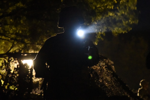 A ROTC cadet from Angelo State University practices nighttime entry controller procedures during the training exercise held at the mock forward operating base on Goodfellow Air Force Base, Texas, April 20, 2018. During the night there was constant simulated bombs, gunfire and shouting. (U.S. Air Force photo by Airman 1st Class Seraiah Hines/Released)