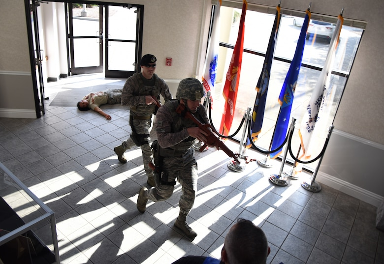 U.S. Air Force Staff Sgt. Timothy Dawson, 81st Security Forces Squadron military working dog handler, left, and Airman 1st Class Michael Booth, 81st SFS installation entry controller, enter the Levitow Training Support Facility during an active shooter exercise at Keesler Air Force Base, Mississippi, April 19, 2018. The wing inspection team had an active duty Air Force member simulate opening fire at the facility in order to test the base's ability to respond and recover from a mass casualty event. (U.S. Air Force photo by Kemberly Groue)