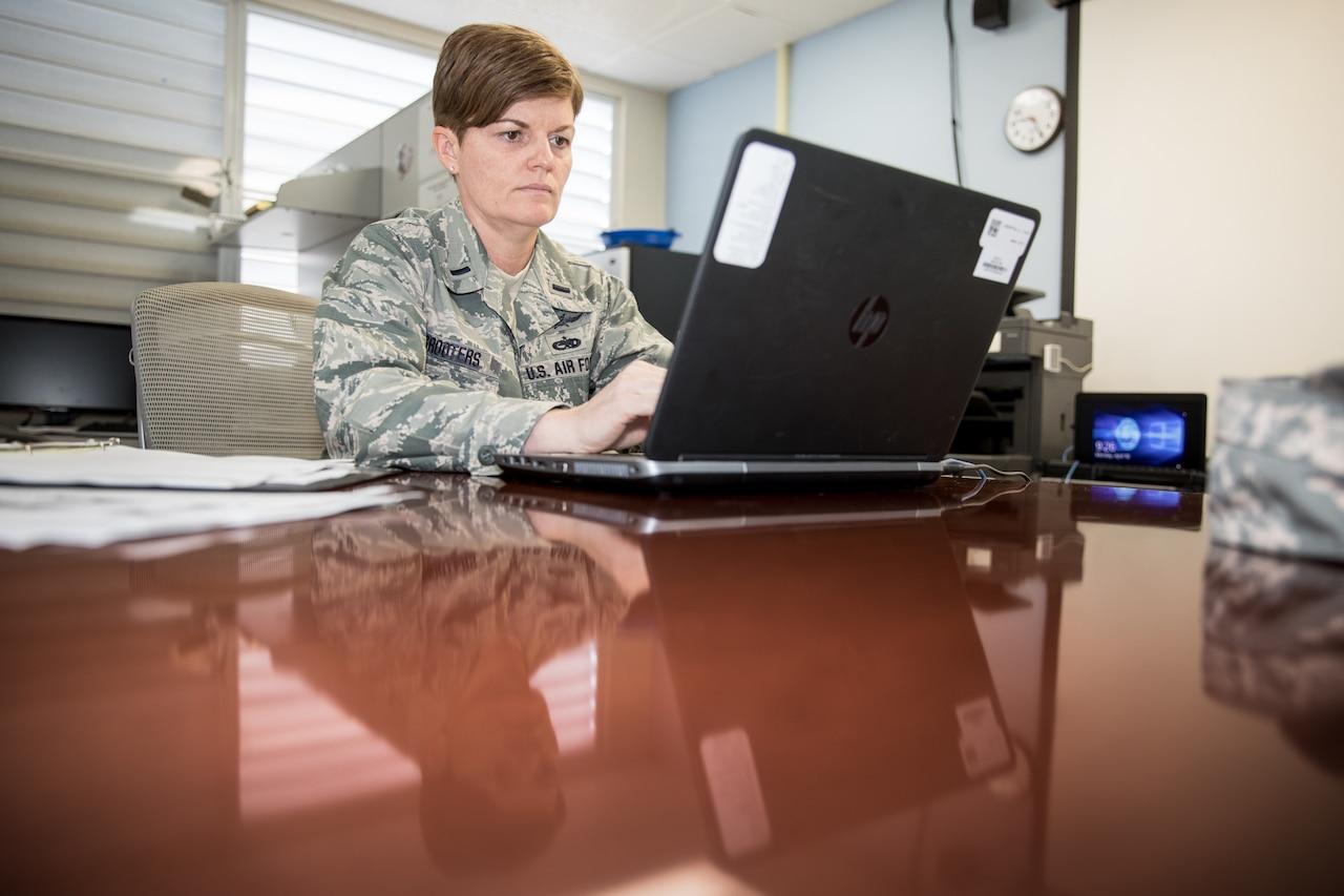 Airman works at laptop computer.